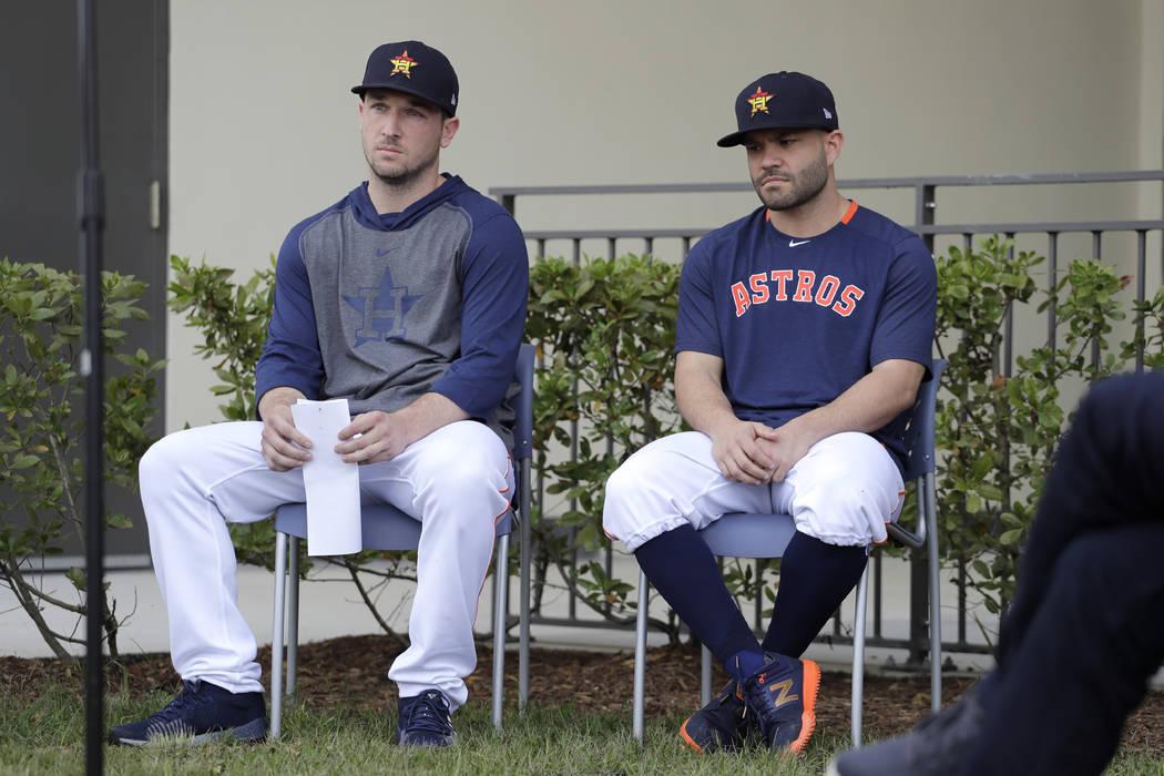 Houston Astros infielder Alex Bregman, left, and teammate Jose Altuve sit in chairs as the wait ...