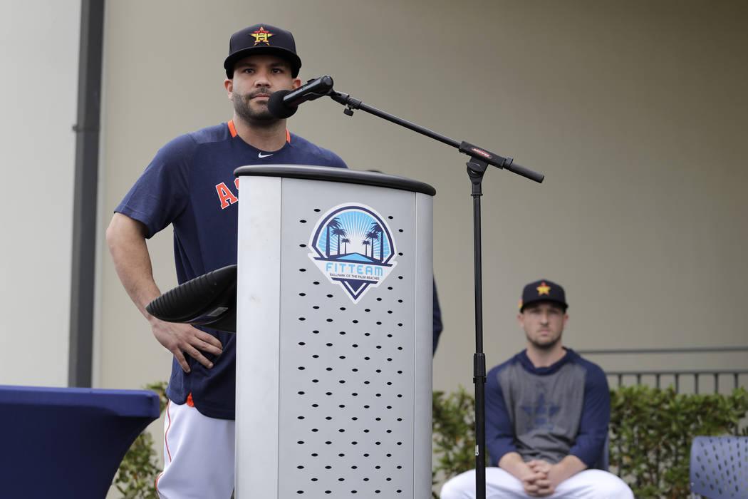 Houston Astros' Jose Altuve speaks at a podium as teammate Alex Bregman, seated right, looks on ...