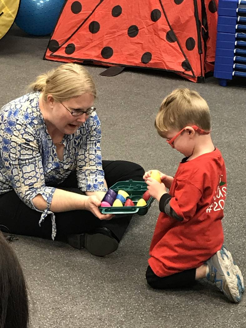Emily Rawlings with Dynamic Music Therapy lets preschooler Levi pick a shaker during a music th ...