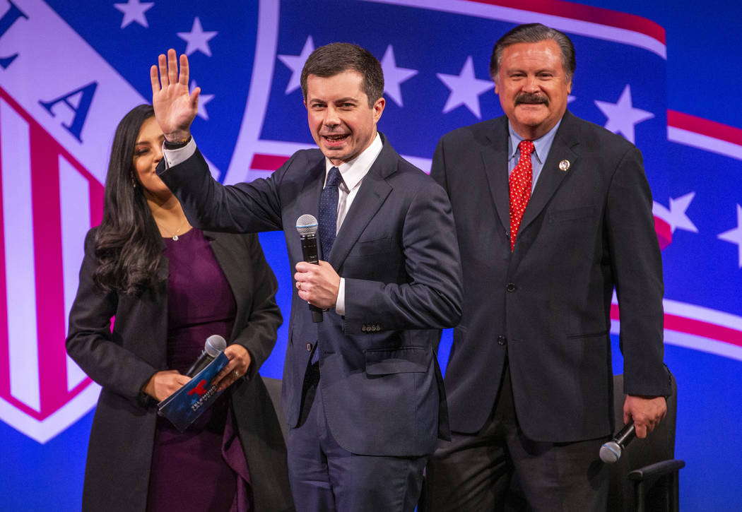 Former South Bend, Ind., Mayor Pete Buttigieg arrives on stage with Leticia Castro and Domingo ...