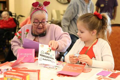 Elise Adoor, 5, center, makes a Valentine's Day themed craft with Barbara Wokosky, 85, at Poet' ...