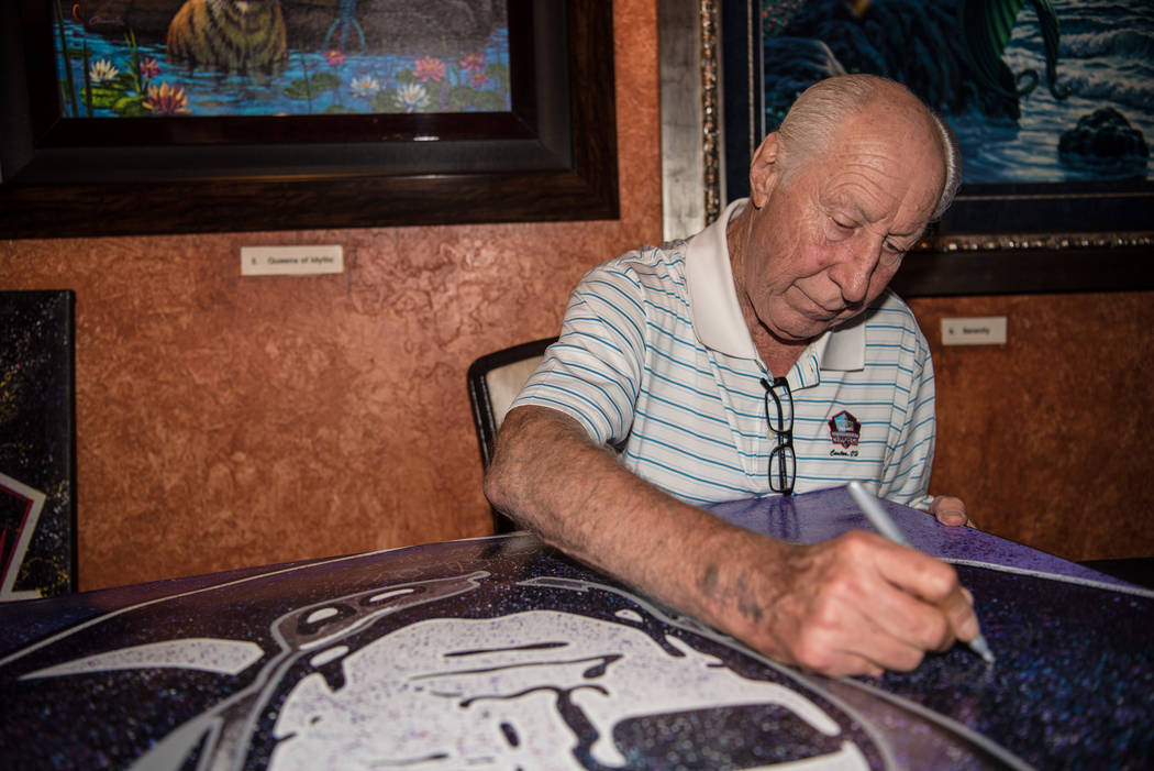 Former Raiders' wide receiver Fred Biletnikoff signs a large canvas at the Mermaid Lounge at Si ...