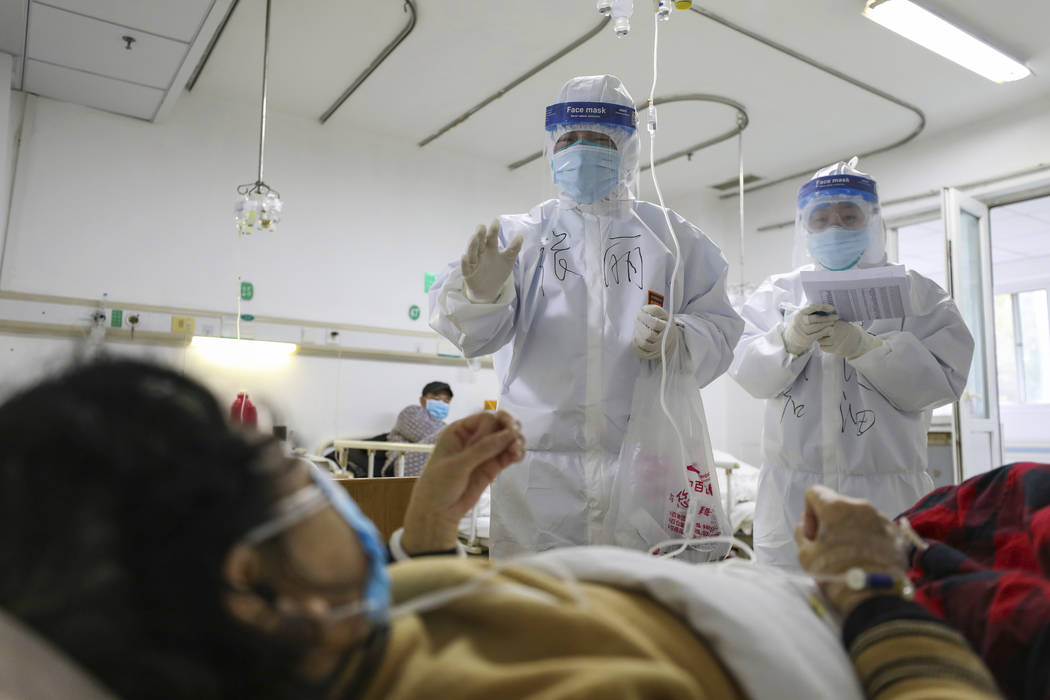 Medical workers check on the conditions of patients in Jinyintan Hospital, designated for criti ...