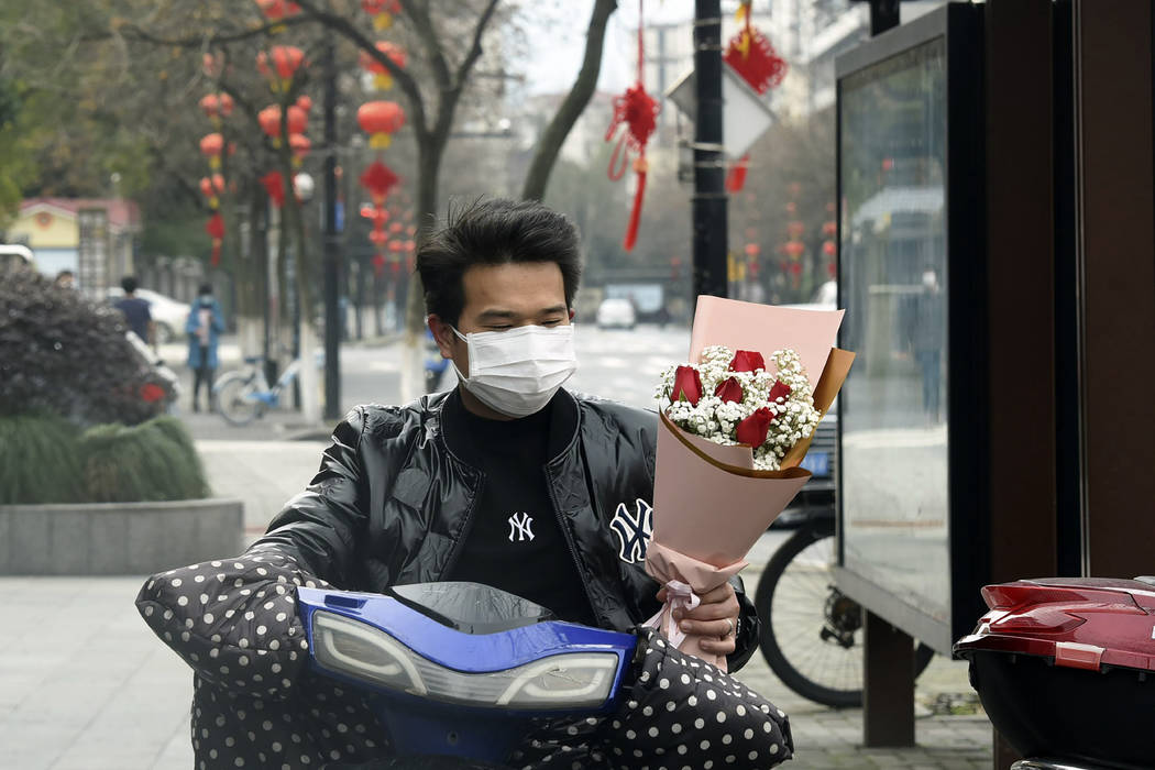 A man wearing a face mask carries a Valentine's Day bouquet as he rides a scooter in Hangzhou i ...