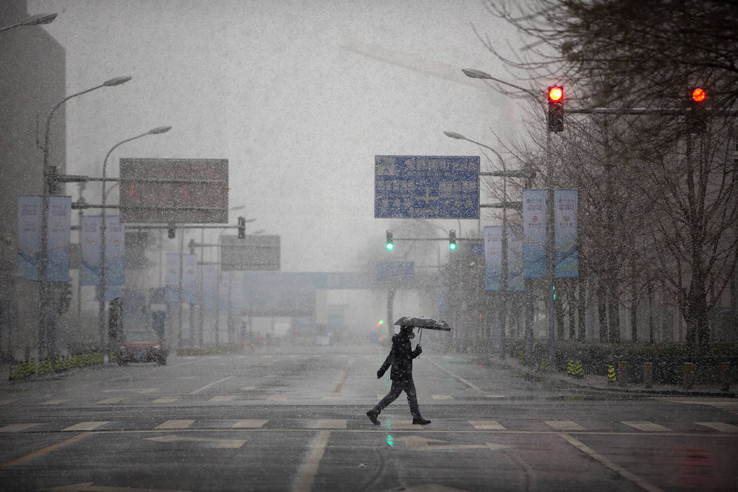 A man wears a mask as he walks across an empty intersection during the morning rush hour as sno ...
