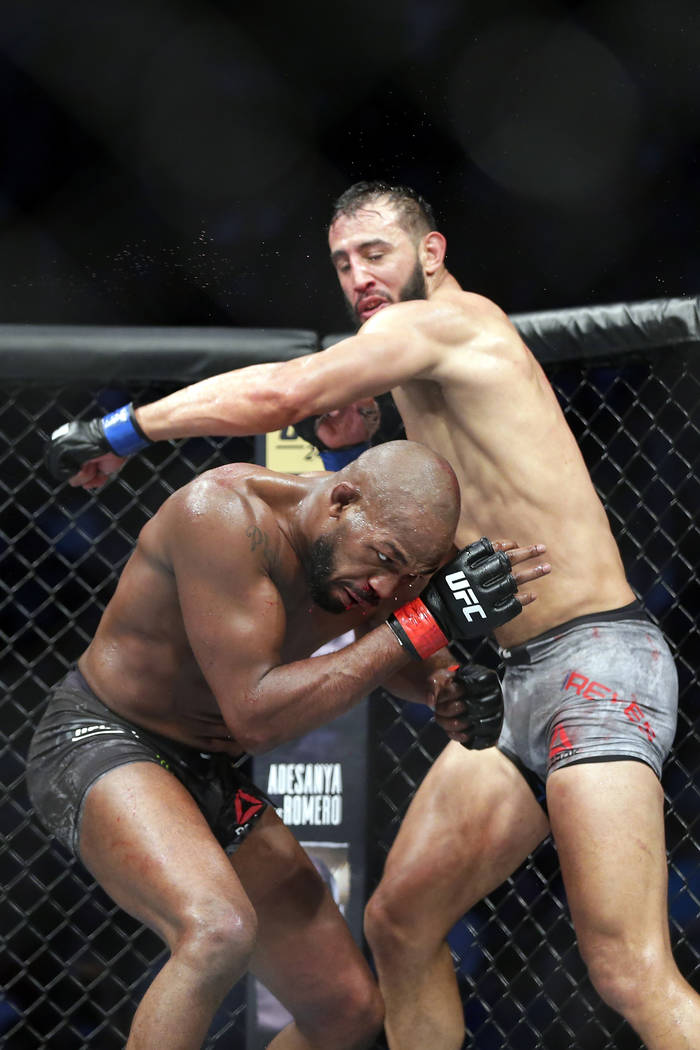 Jon Jones, left, ducks the swing by Dominick Reyes, right, during a light heavyweight mixed mar ...