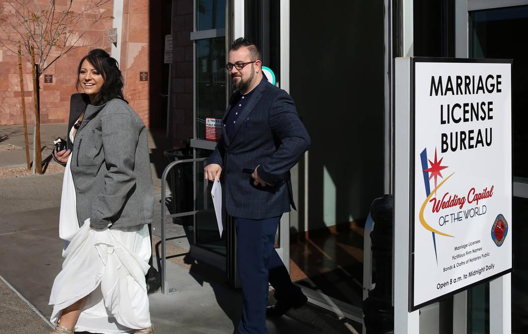Marylyn Barnett, 39, and Trevor Pennock, 35, both of Nebraska, leave the Marriage License Burea ...