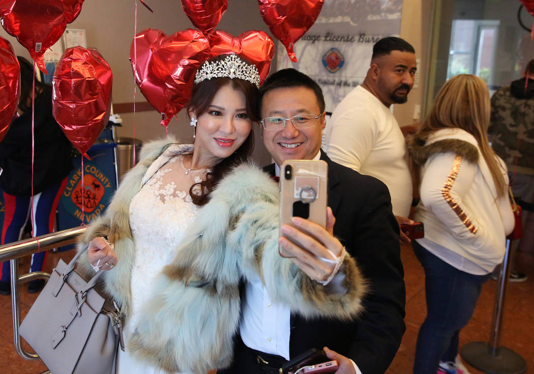 John Zhong and Catherine Li of Los Angeles pose for a selfie as they wait in line to get their ...