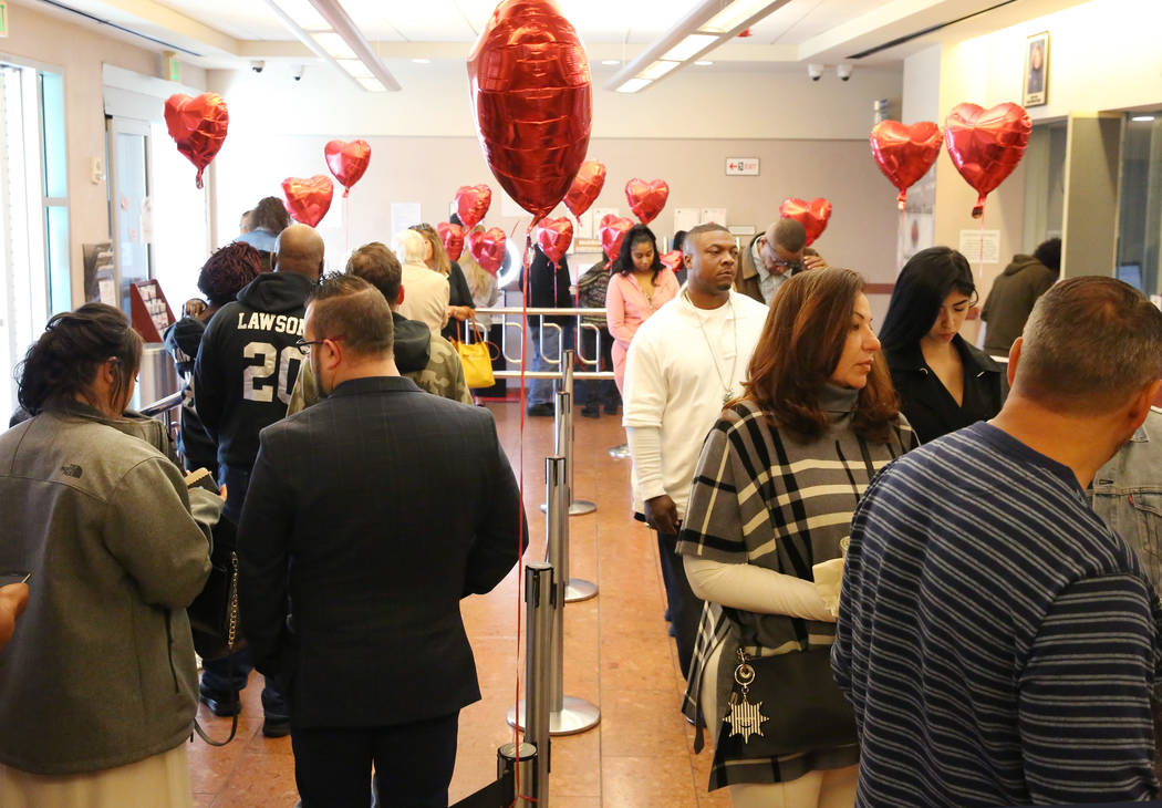 People wait in line at the Marriage License Bureau to get their marriage license on Friday, Feb ...