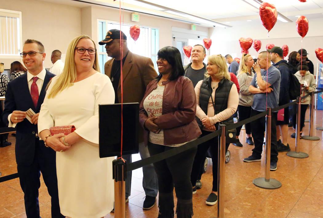 People, including Marylyn Barnett and Trevor Pennock, front, both of Nebraska, wait in line to ...