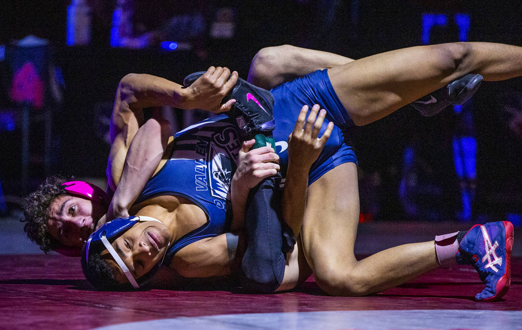 McQueen's Jahaun Hicks, left, wraps up Spring Valley's Ryan Mitchell on the mat in their 113 po ...