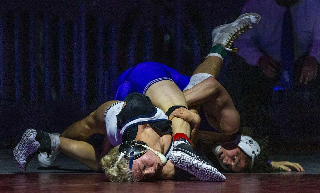 Shadow Ridge's Matthew Van Riel, left, battles on the mat with Spanish Spring's Devin Griffin i ...