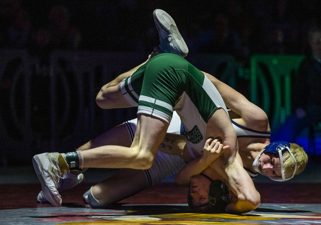 Green Valley's Jeremy Hoffman, left, is driven into the mat by Shadow Ridge's Weston Presser in ...