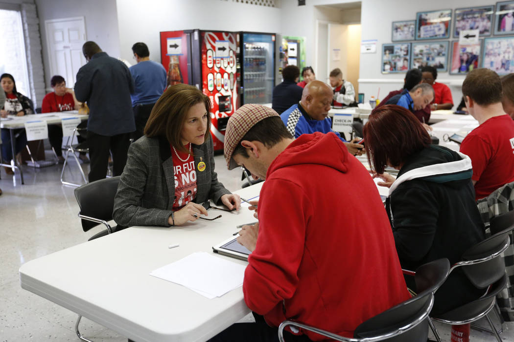 Sen. Catherine Cortez Masto, D-Nev., left, is seen at a check-in table on the first day of earl ...