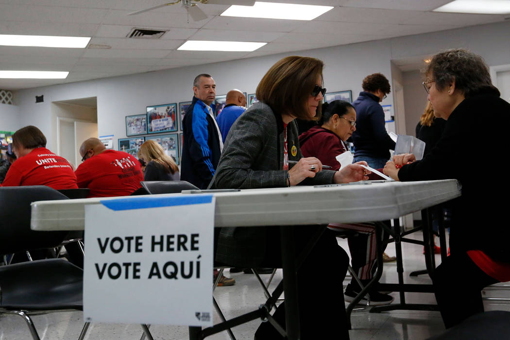 Sen. Catherine Cortez Masto, D-Nev., center fill out a paper ballot on the first day of early v ...