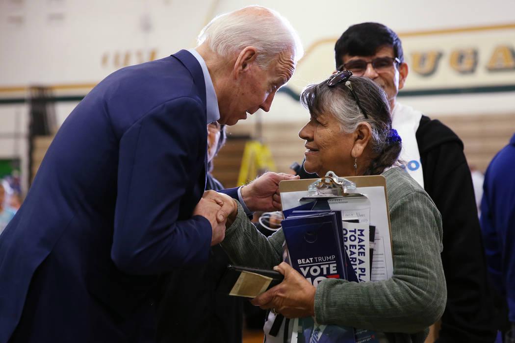 Democratic Presidential Candidate Joe Biden, left, speaks to campaign volunteer Rosie Martinez ...