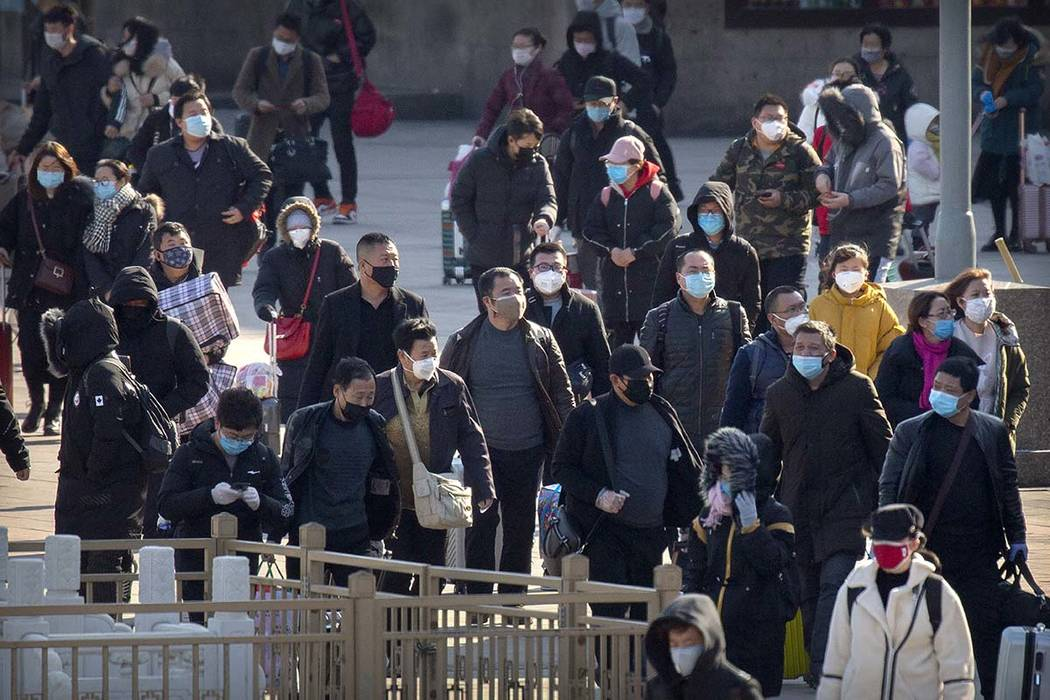 Travelers wear face masks as they walk outside the Beijing Railway Station in Beijing, Saturday ...