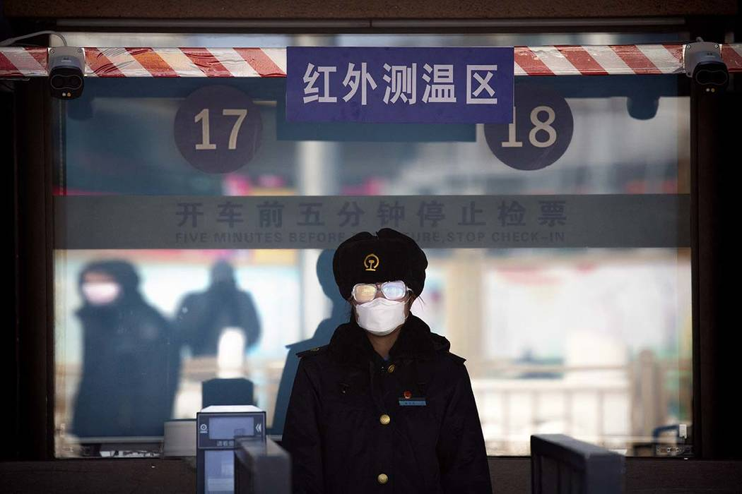 A station worker wears a face mask and goggles as she waits to check passengers' tickets at the ...