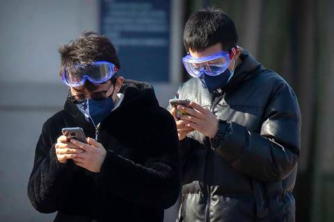 Travelers wear face masks and goggles as they use their smartphones outside the Beijing Railway ...