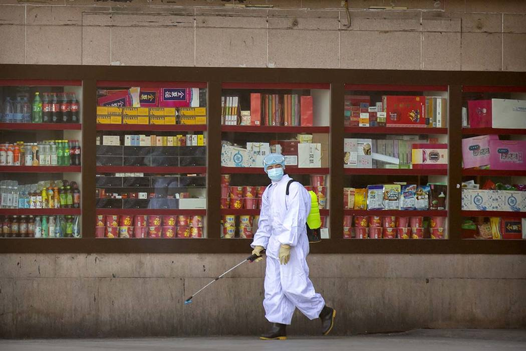 A worker sprays disinfectant outside the Beijing Railway Station in Beijing, Saturday, Feb. 15, ...