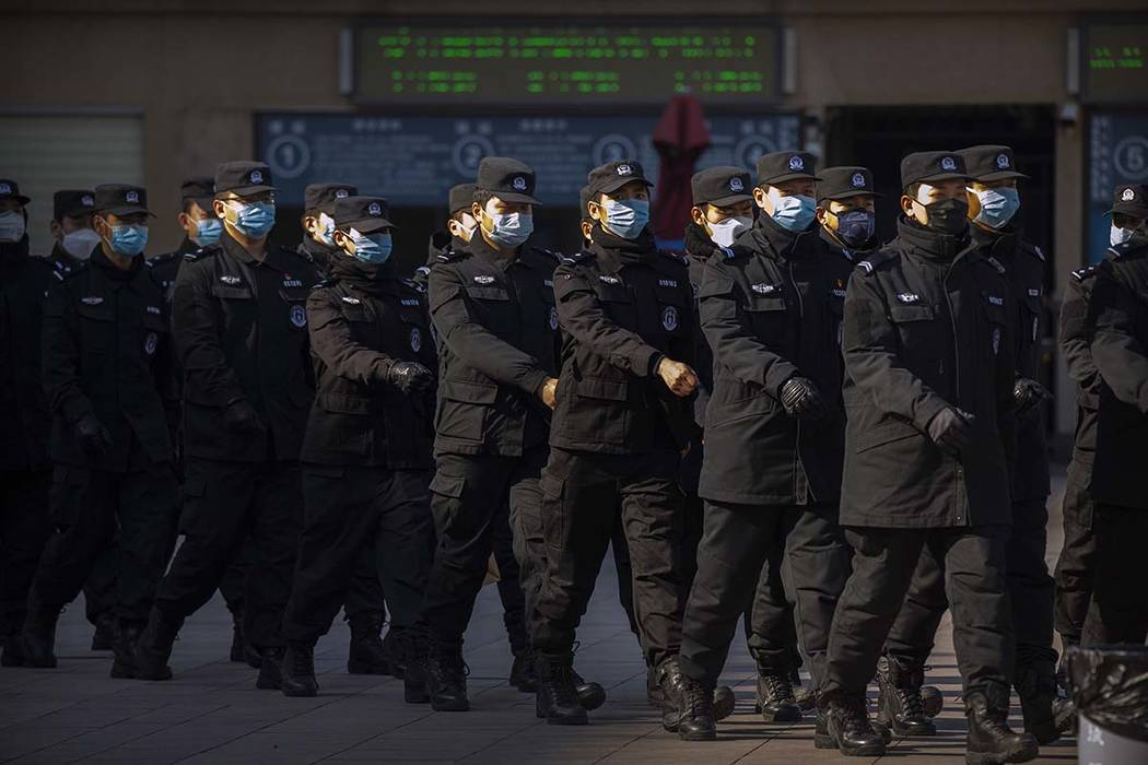 Policemen wear face masks as they march in formation outside the Beijing Railway Station in Bei ...