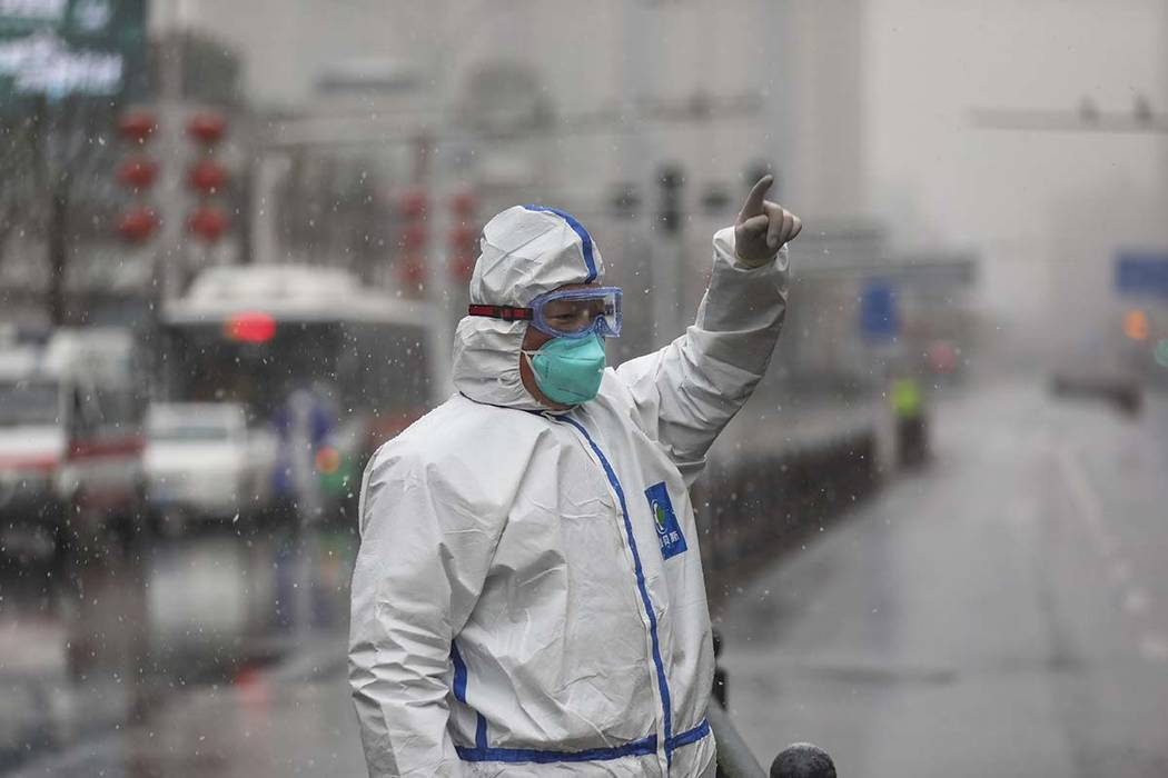 A worker wearing a protective suit gestures to a driver outside a tumor hospital newly designat ...