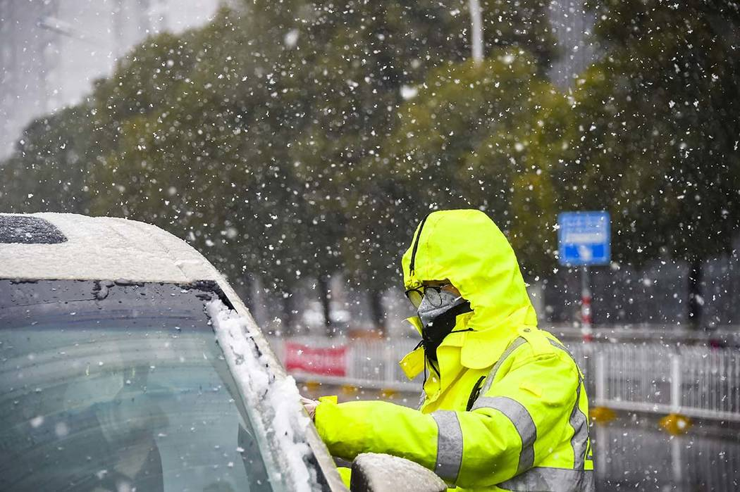 In this photo released by China's Xinhua News Agency, a traffic policeman wearing a face mask c ...