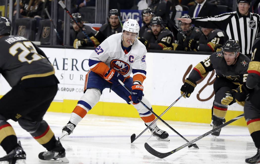New York Islanders forward Anders Lee (27) looks to pass the puck as Vegas Golden Knights cente ...