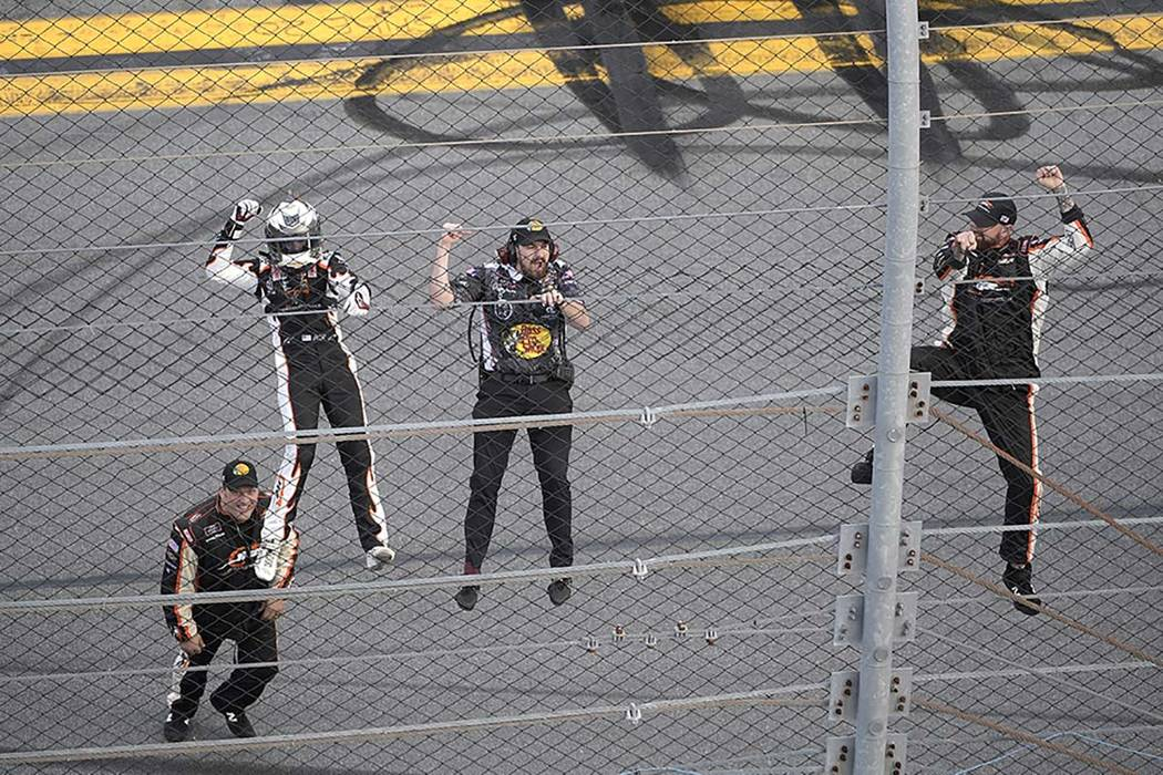 Noah Gragson, left, and crew members celebrate by climbing onto the grandstands safety fence af ...