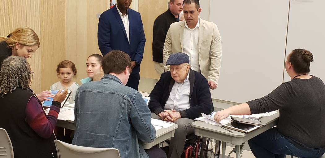 Former Senate Majority Harry Reid checks in with a volunteer at the Nevada State Democratic Par ...