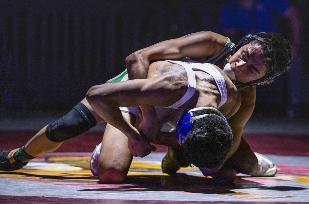 Reed's Alejandro Casarez, left, is dominated from behind by Green Valley's David Kalayanaprapru ...