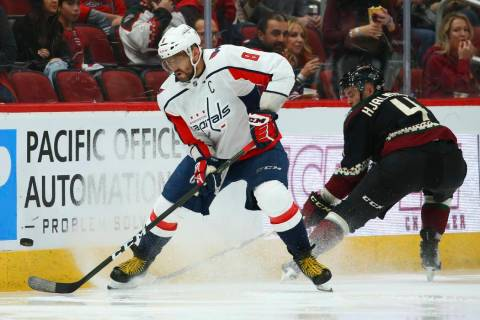 Washington Capitals left wing Alex Ovechkin (8) tries to control the puck in front of Arizona C ...