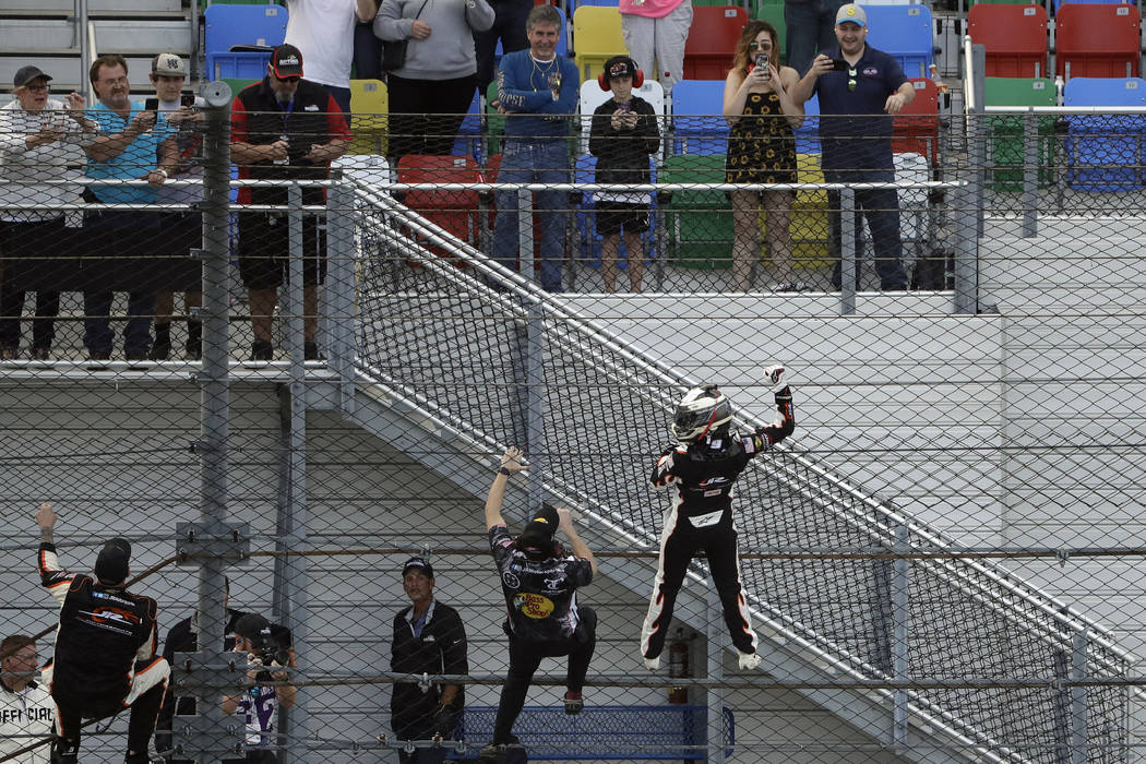 Noah Gragson, lower right, climbs the catch fence as he celebrates his win in the NASCAR Xfinit ...