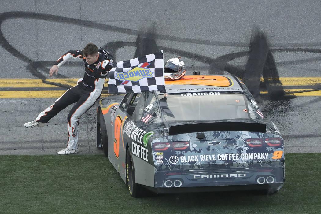 Noah Gragson slides across the hood of his car as he celebrates winning the NASCAR Xfinity seri ...