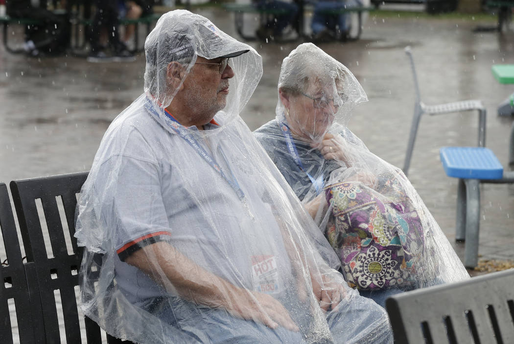 Race fans sit on a bench in the Fan Zone after rain stopped the NASCAR Daytona 500 auto race at ...