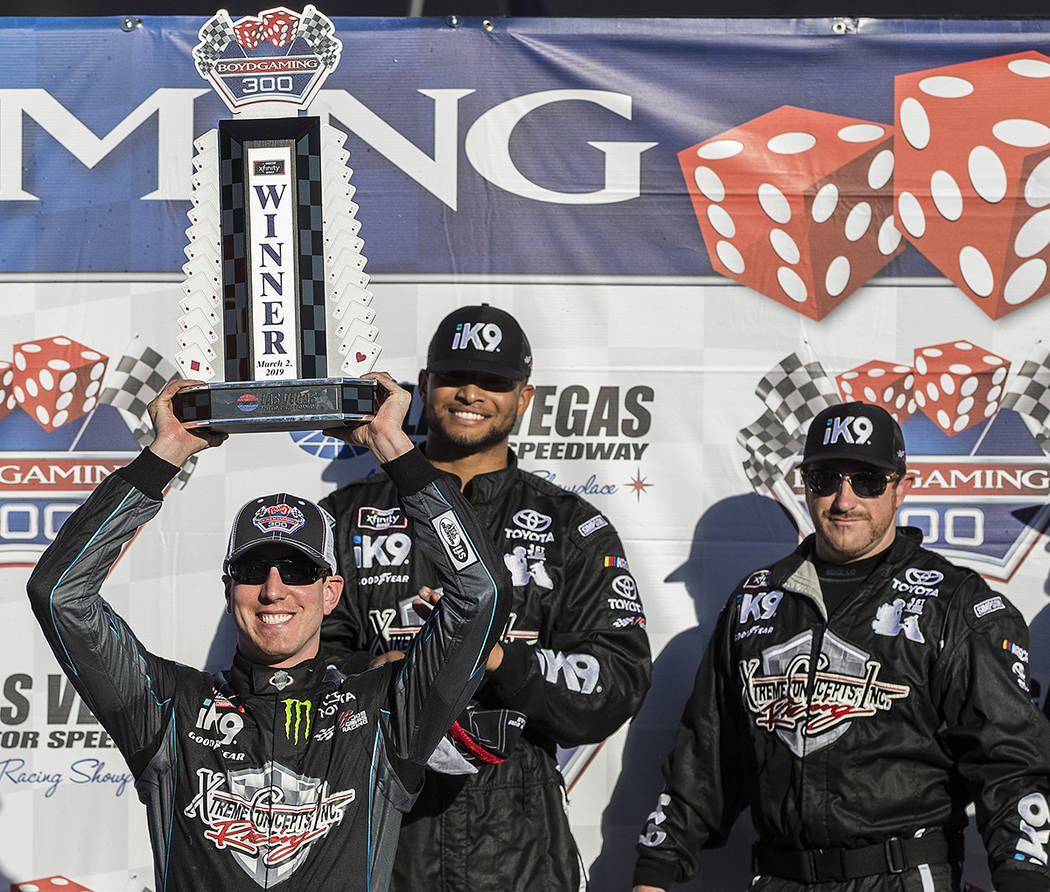 Kyle Busch, left, hoists the trophy for winning the NASCAR Xfinity Series Boyd Gaming 300 on Sa ...