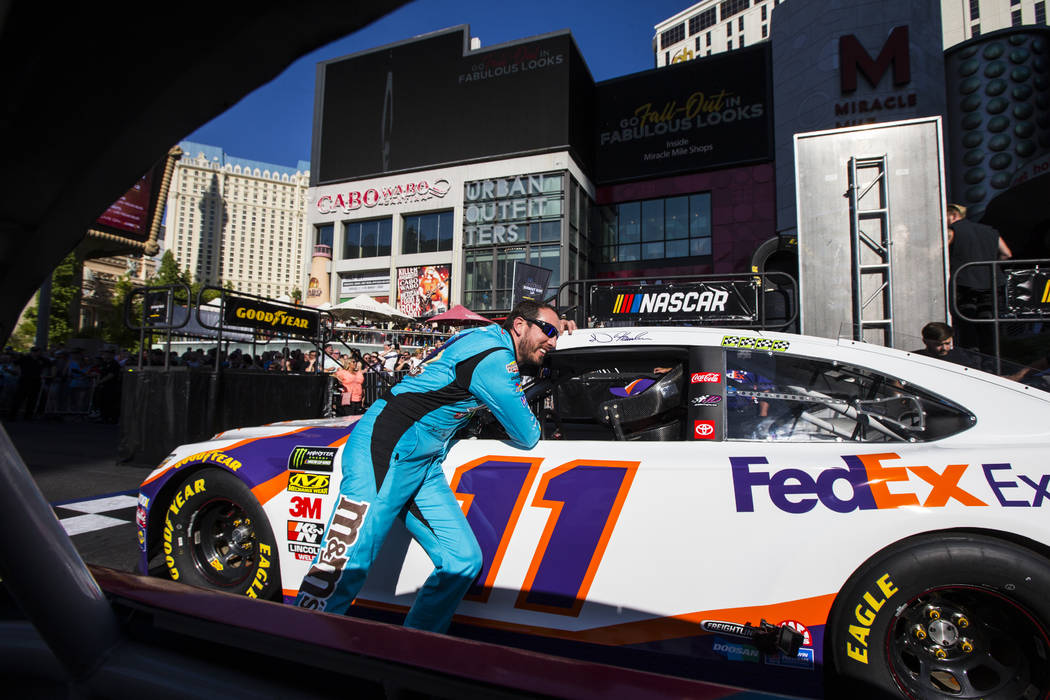 Kyle Busch talks with Denny Hamlin before partaking in the NASCAR America Burnout Boulevard eve ...