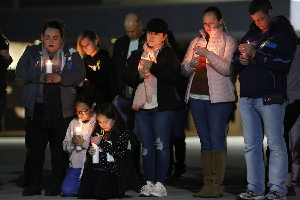 Dozens of parents and students pray during a candlelight vigil at Somerset Academy in North Las ...