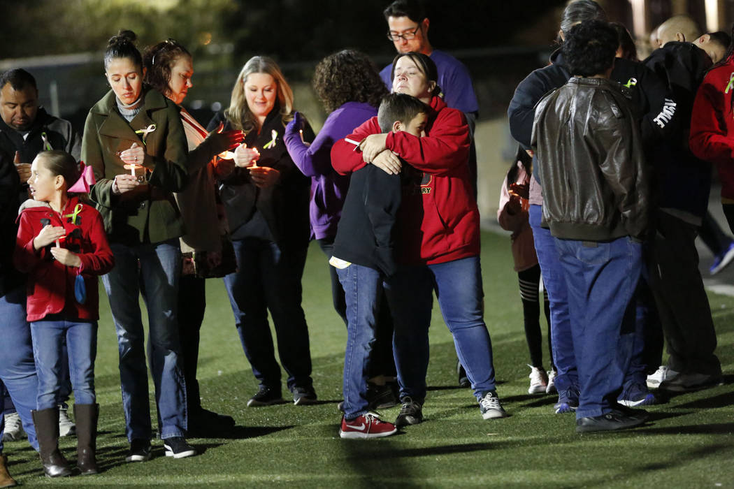Dozens of parents and students hold candles during a candlelight vigil at Somerset Academy in N ...