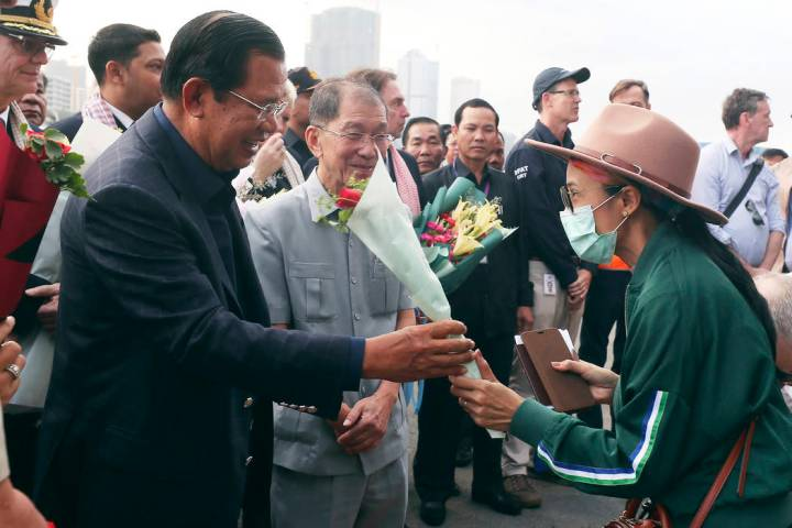 In a Feb. 14, 2020, file photo, Cambodia's Prime Minister Hun Sen, left, gives a bouquet of flo ...