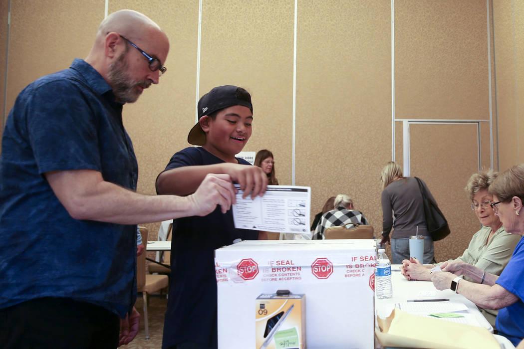 Preston Ribeiro-Salavea, 10, of Henderson helps his father Scott Ribeiro, 56, drop his ballot d ...