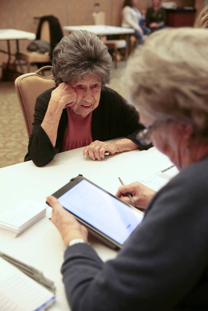 Joann Dunn, 99, checks in with volunteer Ramonda Haycocks, both of Henderson, during early voti ...