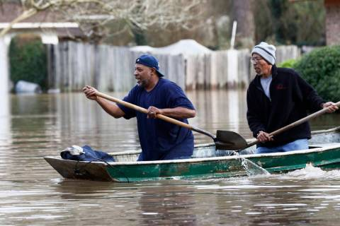 Jackson, Miss., homeowners use shovels to work their way through Pearl River floodwater in this ...