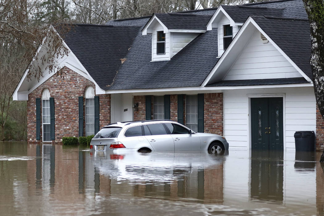 Water from the Pearl River floods this northeast Jackson, Miss., home and car, Sunday, Feb. 16, ...