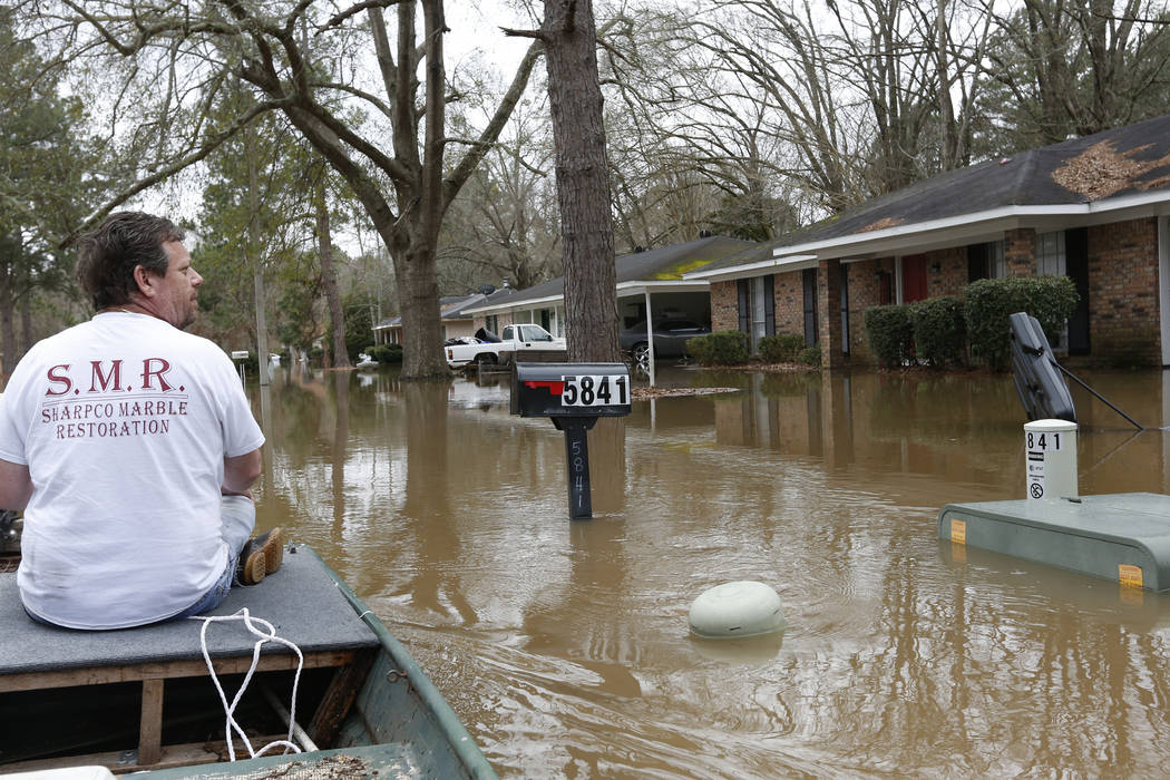 Chris Sharp studies the water damage from the Pearl River that floods his neighborhood in Jacks ...