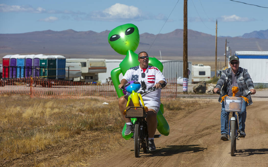 Eric Harvey, left, and Jason Webster of Orange County cruise around the parking area with alien ...