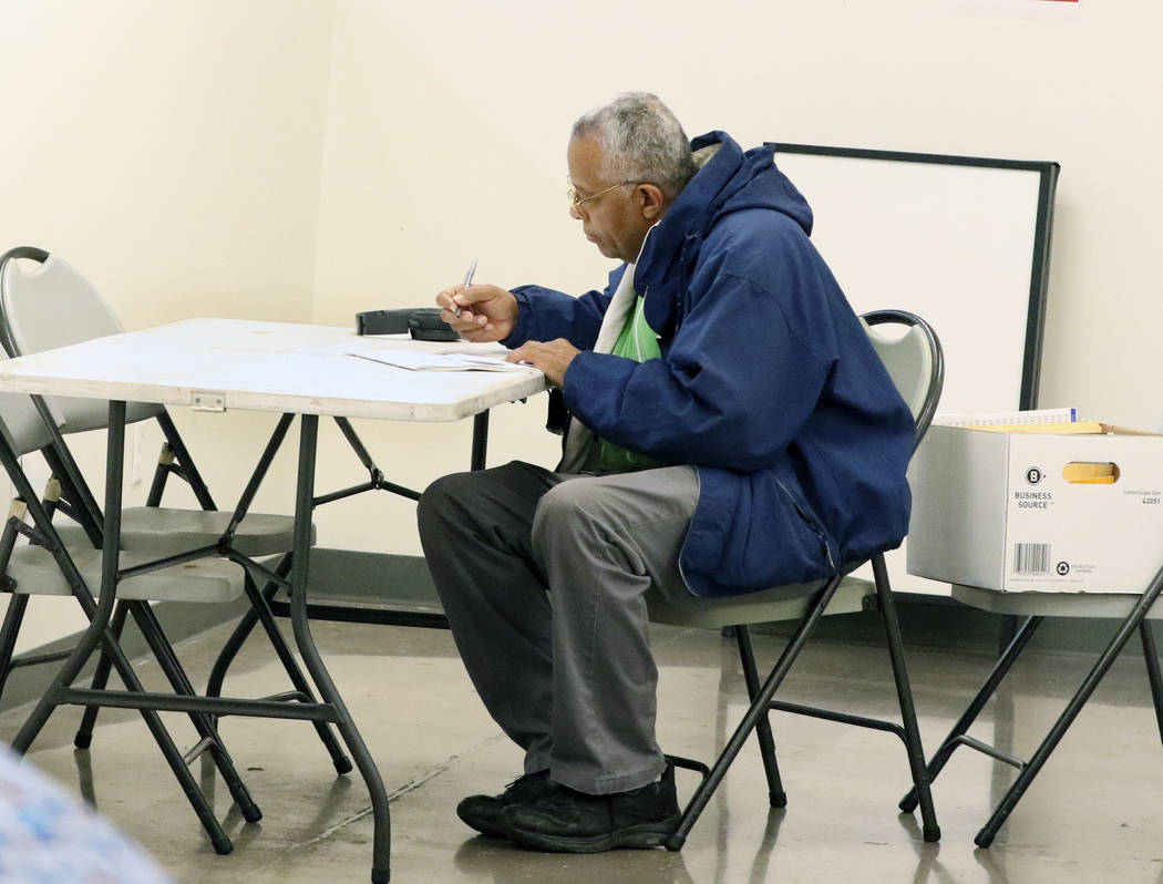 Reginald Bates selects candidates during the last day of early voting in the Nevada Democratic ...