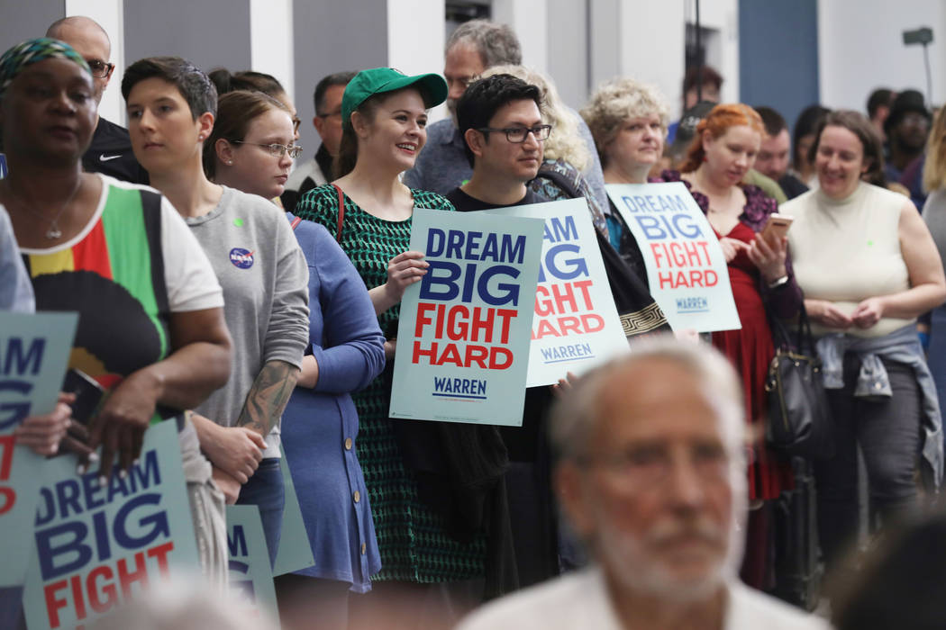 Supporters hold signs and listen as Sen. Elizabeth Warren speaks ahead of a town hall at Colleg ...