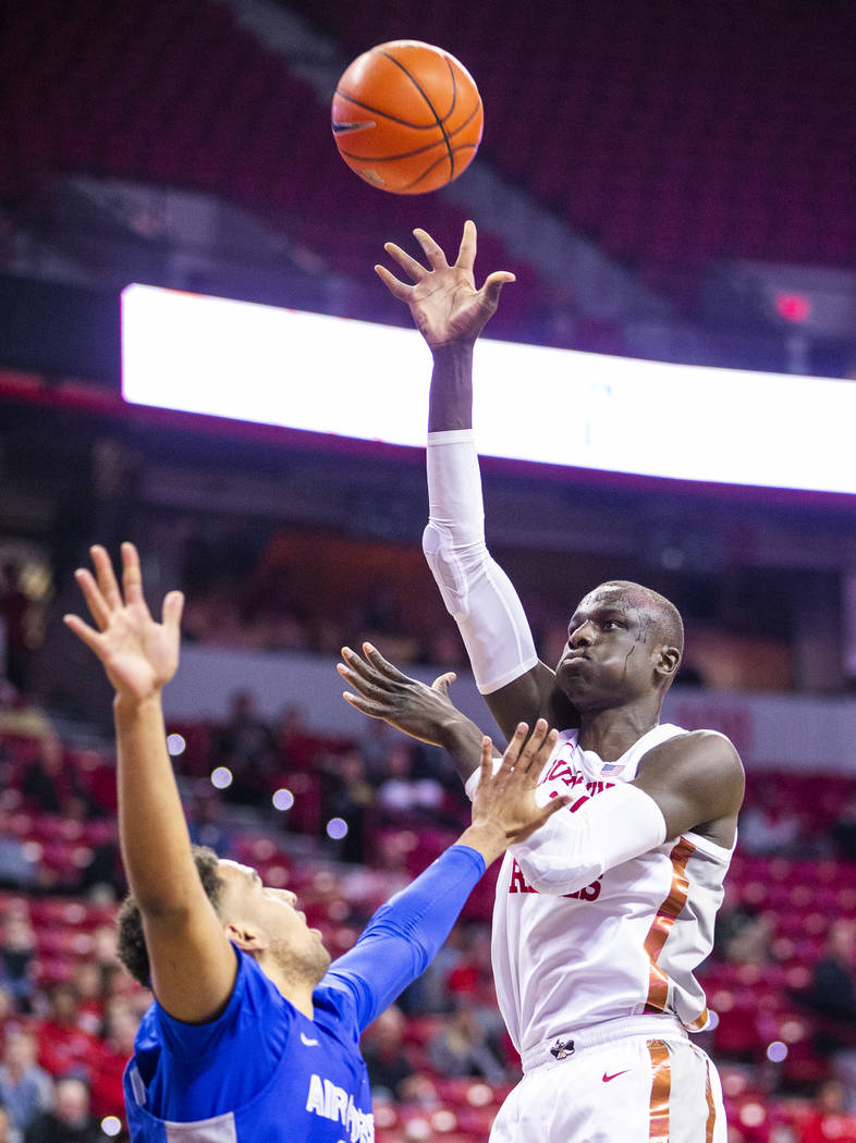 UNLV Rebels forward Mbacke Diong (34, right) lets go a shot over Air Force Falcons center Ryan ...