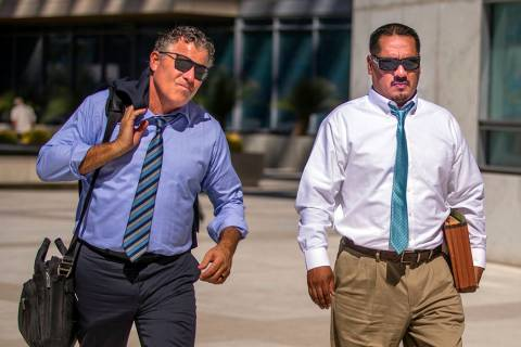 Counselor Mark Fleming, left, walks out with defendant Albert Lopez outside the Lloyd D. George ...
